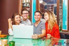 小组有膝上型计算机的愉快的人在咖啡馆 免版税库存图片