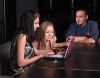 小组有膝上型计算机的年轻学生在咖啡馆 库存图片