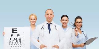 小组有视力检查表的微笑的医生 库存图片