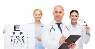 小组有视力检查表的微笑的医生 库存照片