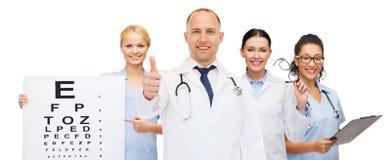 小组有视力检查表的微笑的医生 免版税库存图片