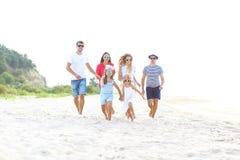 小组有跑在海滩的孩子的朋友 免版税库存照片