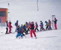 小组有辅导员的小滑雪者为登上的下降做准备 奥地利, 2015年2月22日的Zams 免版税库存图片