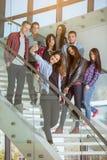 小组有采取selfie的智能手机的微笑的学生 免版税库存照片