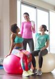 小组有锻炼球的微笑的妇女在健身房 免版税库存照片