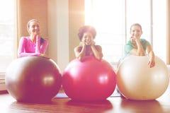 小组有锻炼球的微笑的妇女在健身房 免版税库存图片