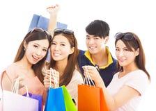 小组有购物袋的愉快的青年人 免版税库存图片