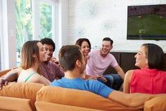 小组朋友一起坐沙发观看的足球 免版税库存图片