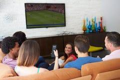小组朋友一起坐沙发观看的足球 免版税库存照片