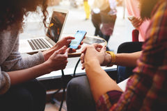 小组朋友使用小配件在休闲时间在咖啡店 免版税库存图片