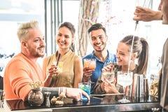 小组朋友喝鸡尾酒和谈话在餐馆 免版税库存图片