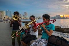 小组朋友在哈瓦那,古巴演奏在Malecon的音乐 图库摄影