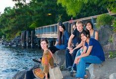 小组年轻朋友坐岩石由湖 免版税库存照片
