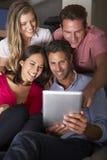 小组朋友坐看数字式片剂的沙发 免版税库存图片