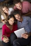 小组朋友坐看数字式片剂的沙发 库存照片