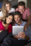 小组朋友坐看数字式片剂的沙发 库存图片