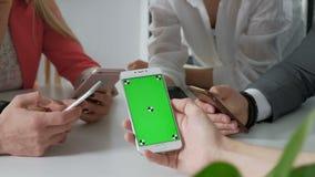 小组朋友获得乐趣与智能手机一起-手社会网络特写镜头与流动手机的- Wifi 影视素材