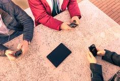 小组年轻朋友获得乐趣与智能手机一起 免版税库存照片