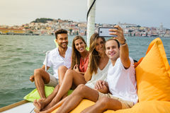 小组朋友获得乐趣在小船在河 免版税库存图片