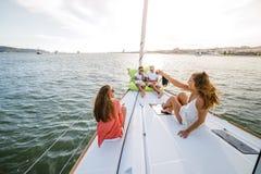 小组朋友获得乐趣在小船在河 免版税图库摄影