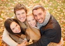 小组朋友获得乐趣在秋天公园 免版税库存照片