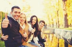 小组朋友获得乐趣在秋天公园 库存图片