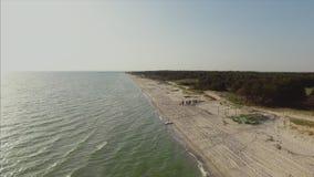 小组朋友通过夏令时的海滩享受松弛步行在日落 从飞过的寄生虫的鸟瞰图 股票视频