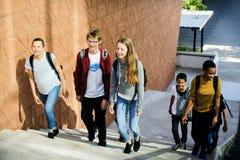 小组步行沿着向下楼梯的学校朋友 免版税库存照片