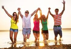 小组海滩的愉快的少年 免版税库存照片