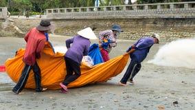小组渔夫拉扯鱼网 免版税图库摄影