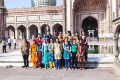 小组游人为在Jama Masjid清真寺前面的一张照片摆在老德里 图库摄影