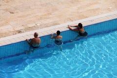 小组游人采取水处理在游泳池 库存图片