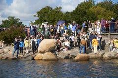 小组游人临近小的美人鱼雕象 免版税库存照片