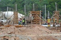 小组熔铸为地面水泥板的建筑工人 库存照片