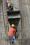 小组熔铸地面水泥板的建筑工人 免版税库存照片
