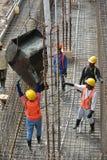 小组熔铸地面水泥板的建筑工人 图库摄影