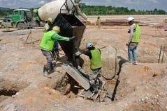 小组熔铸桩帽的建筑工人 免版税库存图片
