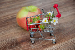 小购物车用草莓临近在木背景的苹果 免版税库存图片