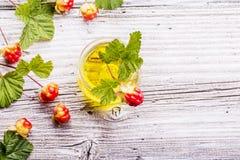 小玻璃瓶子用罕见的北野草莓油莓果和叶子在灰色木结构背景 的treadled 图库摄影