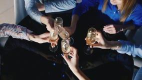 小组从玻璃的青年人饮用的酒使在黑镜子桌的玻璃叮当响 在视图之上 股票录像
