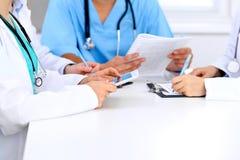 小组医生在医疗会议上 关闭使用片剂计算机的医师 免版税库存照片