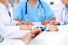 小组医生在医疗会议上 关闭使用片剂计算机的医师 库存图片