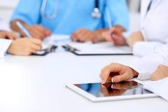 小组医生在医疗会议上 关闭使用片剂计算机的医师 免版税库存图片