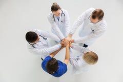 小组医生用一起手在医院 免版税库存图片