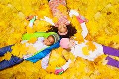 小组男孩和女孩槭树的离开 免版税库存图片