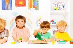 小组男孩在有玩具工作工具的教室 库存照片