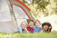 小组男孩获得乐趣在帐篷在乡下 免版税图库摄影