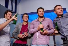 小组男性朋友用啤酒在夜总会 免版税图库摄影
