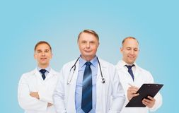 小组白色外套的微笑的男性医生 库存图片