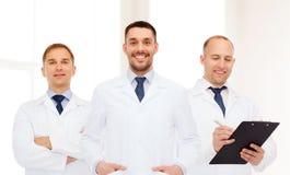 小组白色外套的微笑的男性医生 免版税图库摄影